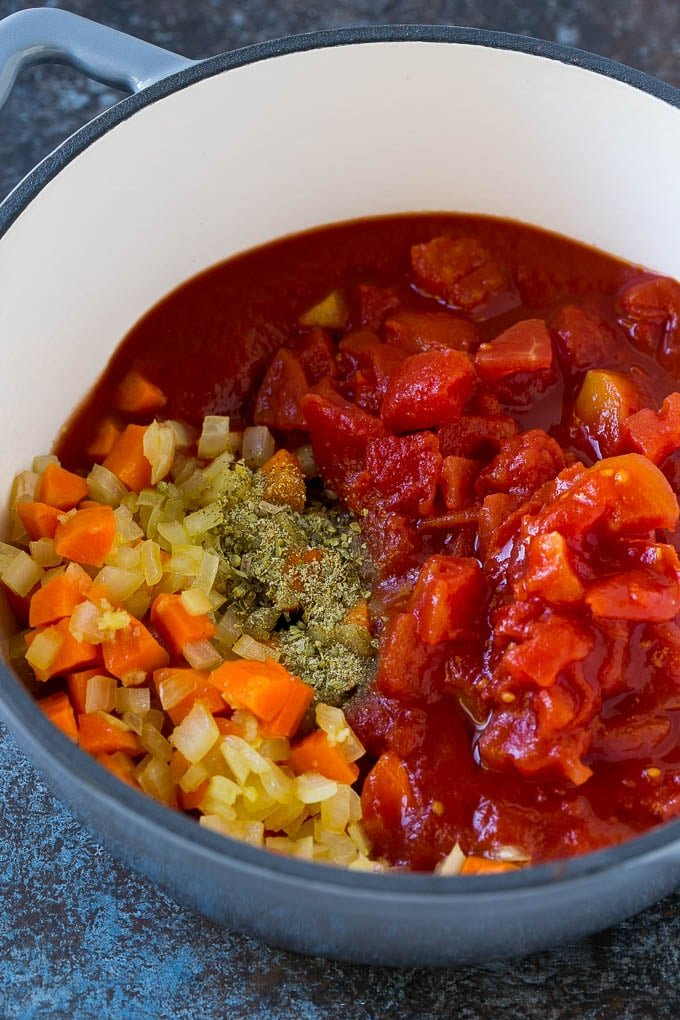 Vegetables, tomatoes and herbs in a soup pot.