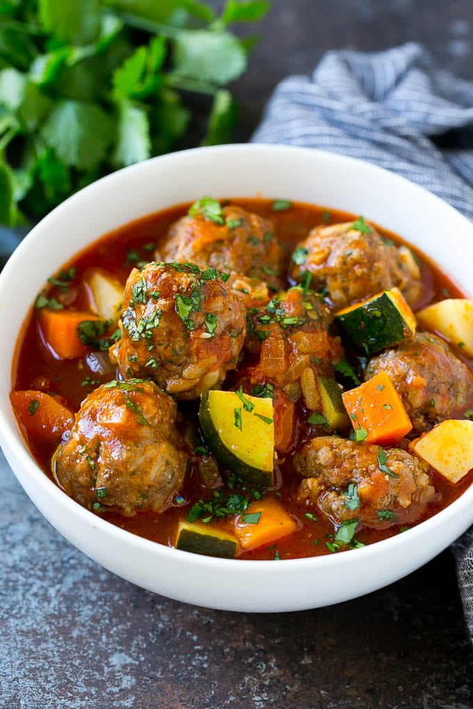 A bowl of albondigas soup with meatballs, carrots, zucchini and tomatoes.