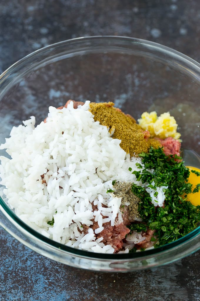 Ground beef, rice, herbs and garlic in a mixing bowl.