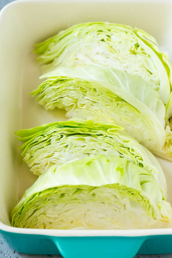 Wedges of cabbage in a baking dish.