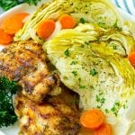 A plate of grilled chicken along with braised cabbage, carrots and onions.