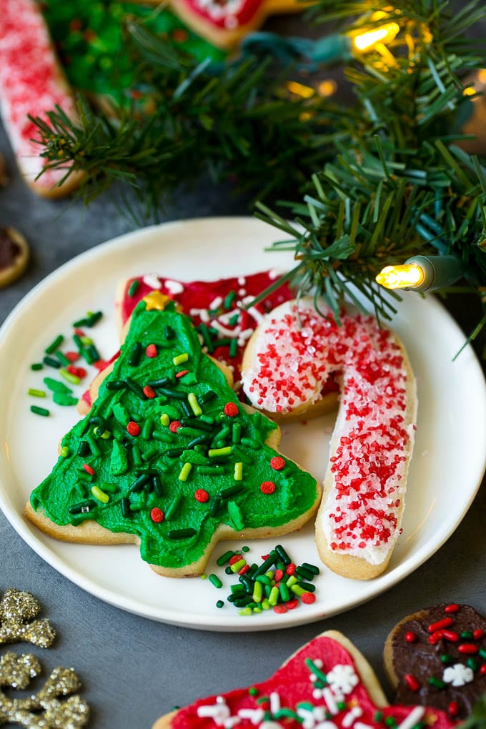 A selection of Christmas sugar cookies served on a plate, with holiday decorations in the background.