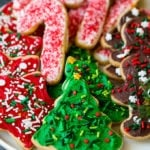 A serving plate of Christmas sugar cookies decorated with frosting and sprinkles.