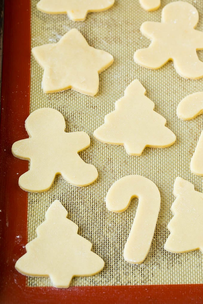 Cookie dough cut into holiday shapes on a baking sheet.