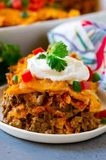 A piece of Dorito casserole with layers of tortilla chips, beef and cheese.