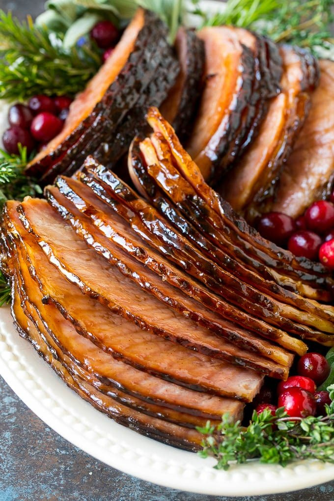 Sliced glazed ham on a serving platter garnished with rosemary, cranberries and sage.