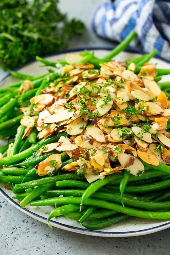 Green beans almondine on a serving plate, topped with toasted sliced almonds and chopped parsley.