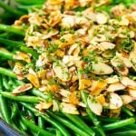 A pan of green beans almondine topped with toasted sliced almonds, butter and chopped parsley.