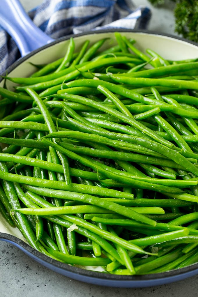 Cooked green beans in shallot butter in a skillet.