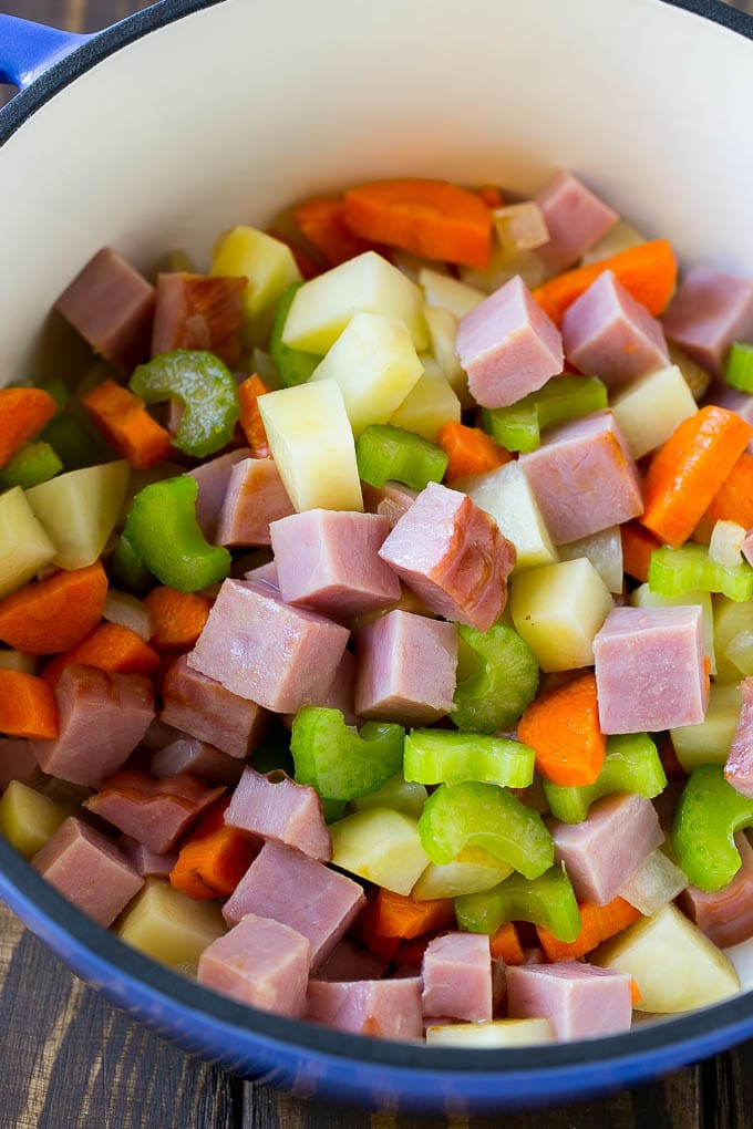 Diced ham, carrots, potatoes and celery in a soup pot.