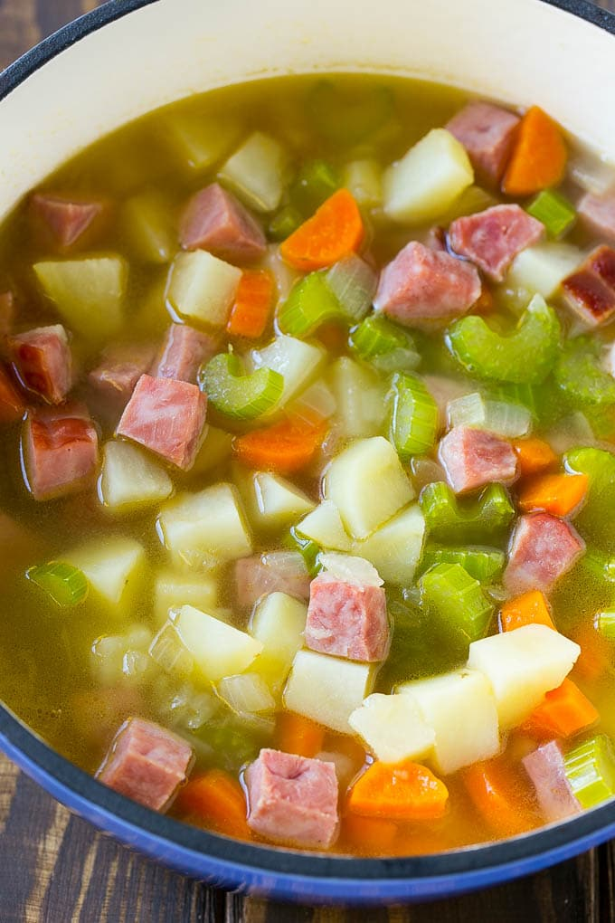 A pot full of ham, potatoes and vegetable simmered in chicken broth.