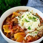 A bowl of lasagna soup topped with ricotta, parmesan and mozzarella cheeses.