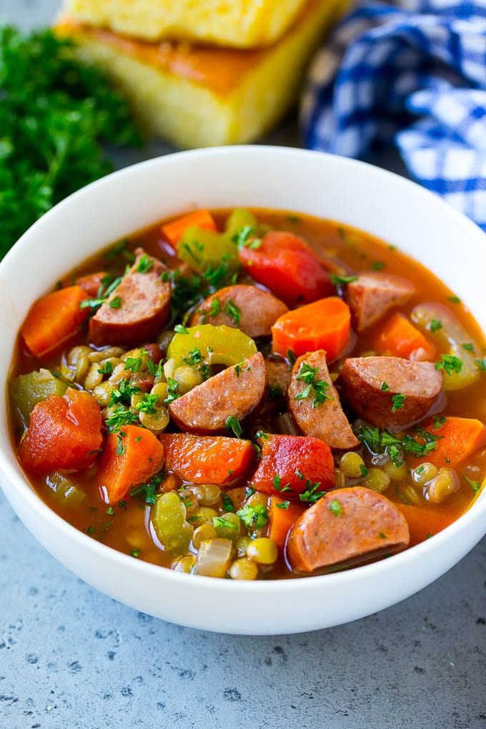 A bowl of lentil soup made with smoked sausage and vegetables.