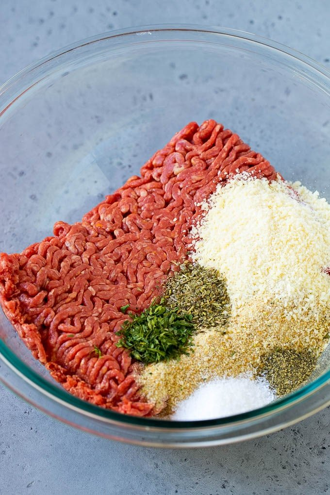Ground beef, breadcrumbs, parsley, herbs and parmesan cheese in a mixing bowl.