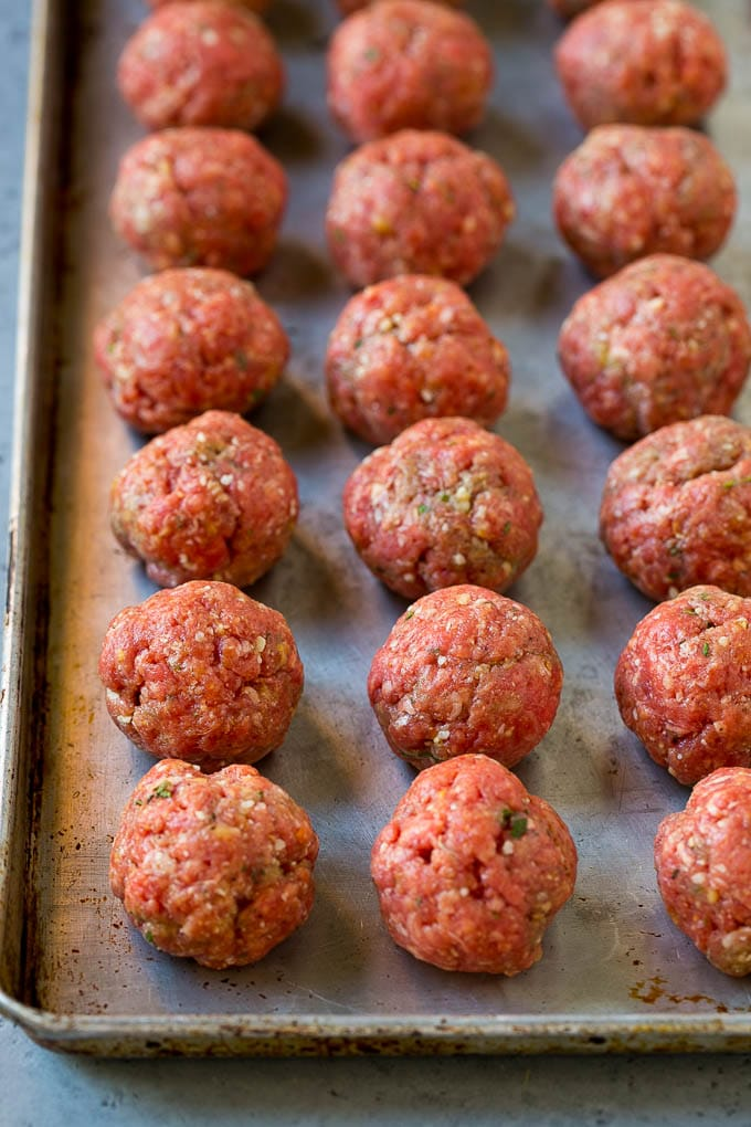 Raw meatballs on a sheet pan ready to go into the oven.