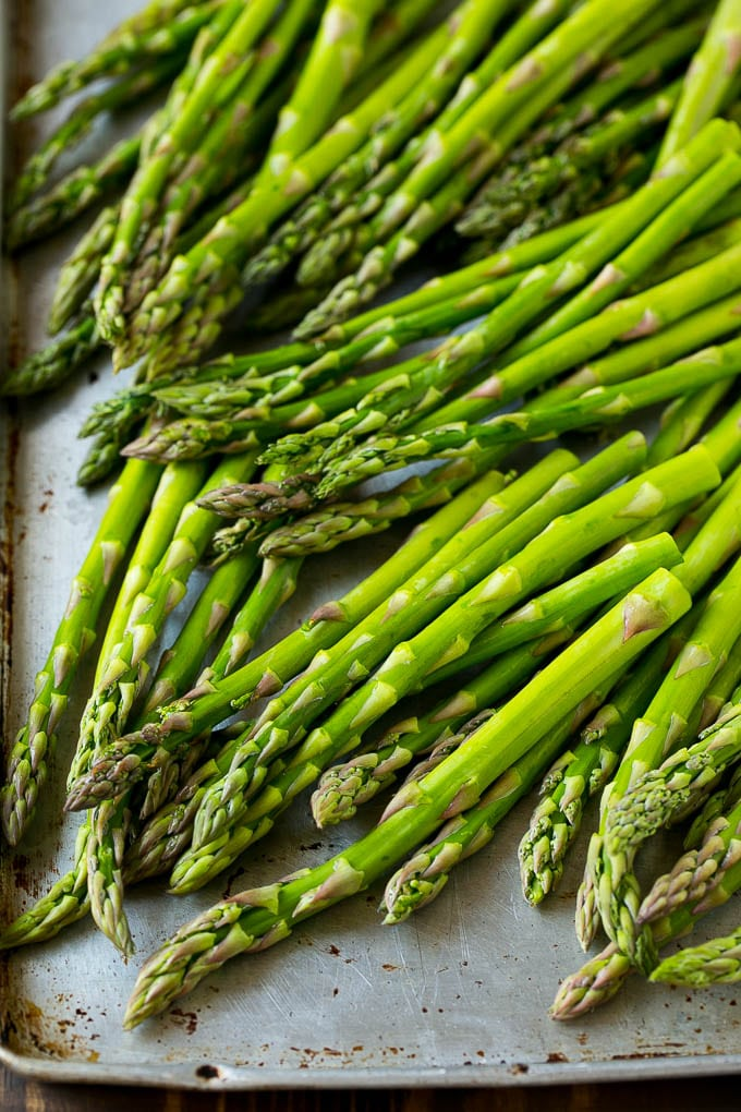 Raw asparagus stalks on a sheet pan.