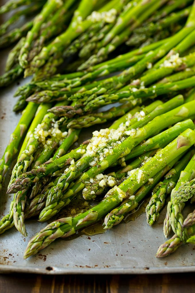Raw asparagus stalks drizzled with olive oil, garlic, herbs, salt and pepper.