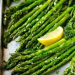 Roasted asparagus on a sheet pan, topped with chopped parsley and garnished with lemon wedges.