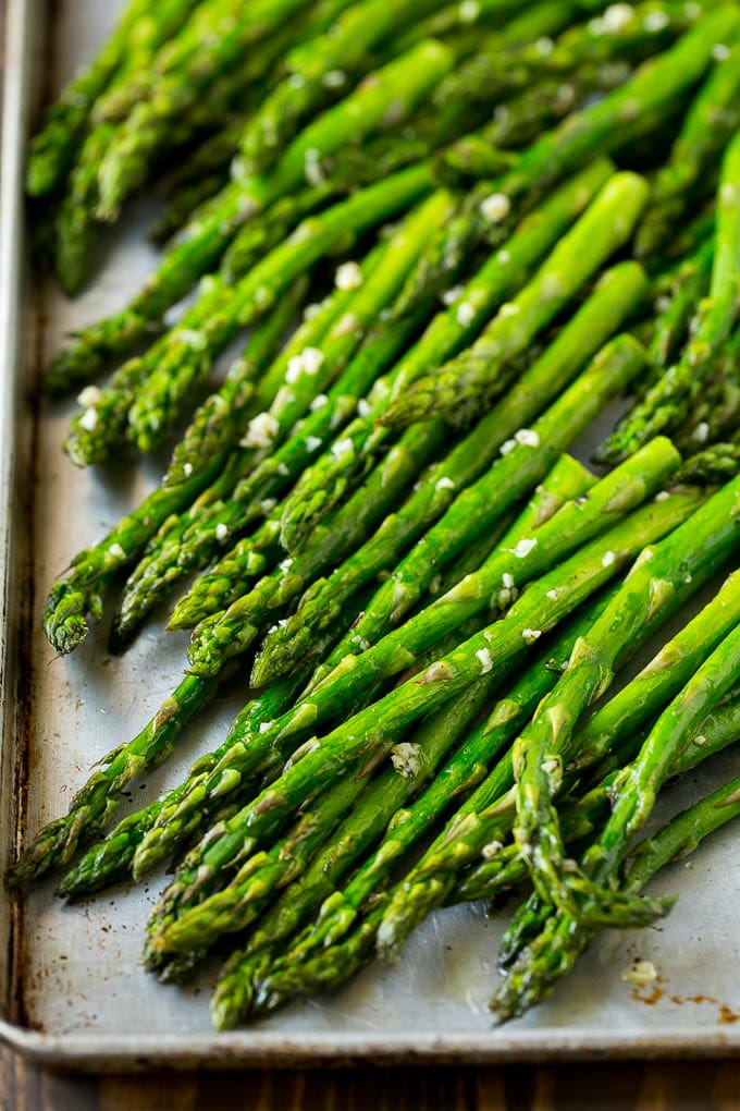 Roasted asparagus with garlic and olive oil on a baking sheet.