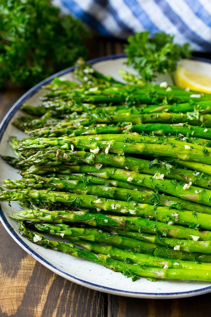 A serving plate of roasted asparagus topped with chopped parsley.