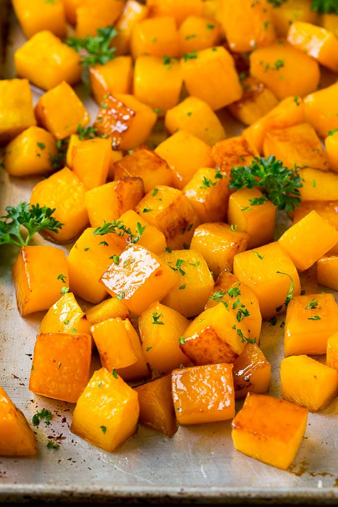Roasted butternut squash with brown sugar and maple syrup, garnished with chopped parsley.
