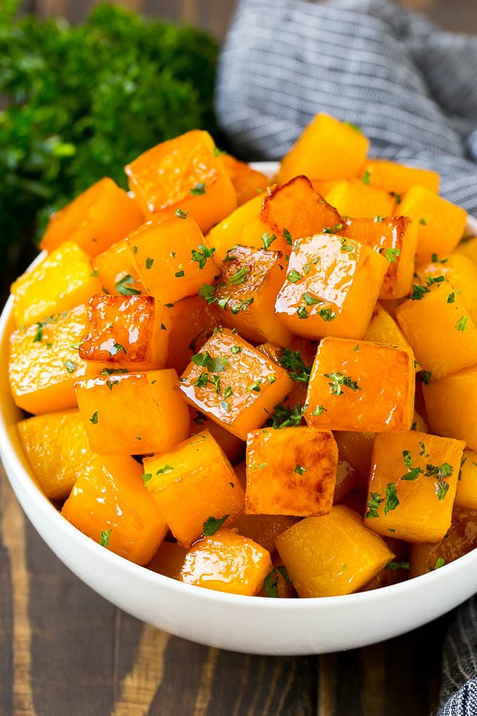 A bowl of roasted butternut squash made with brown sugar and maple syrup, then garnished with chopped parsley.