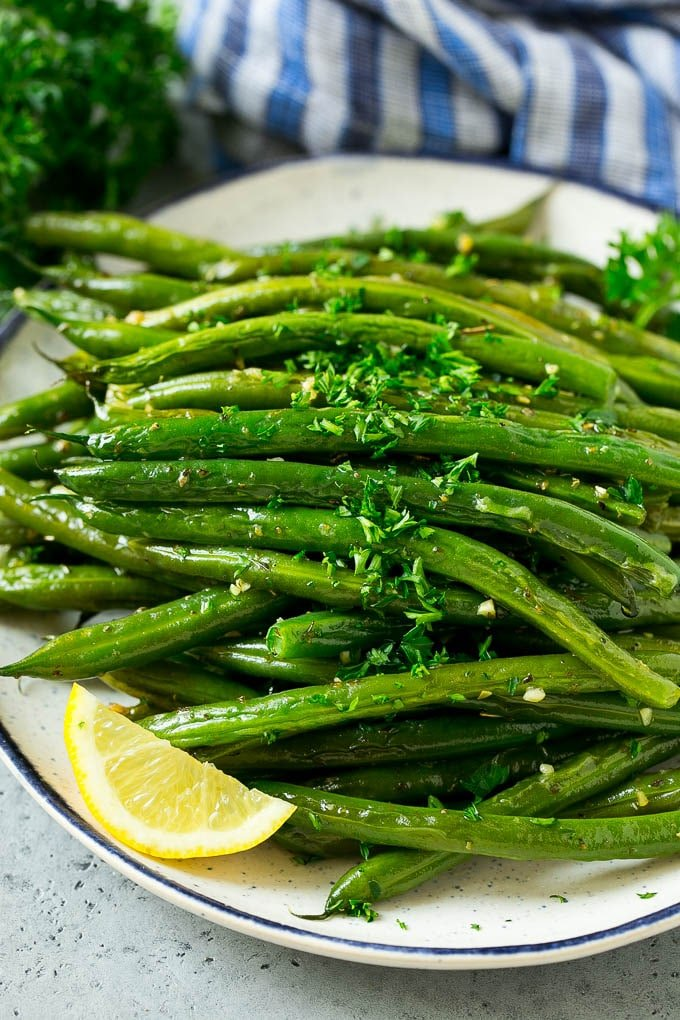 Roasted green beans on a serving plate topped with chopped parsley.