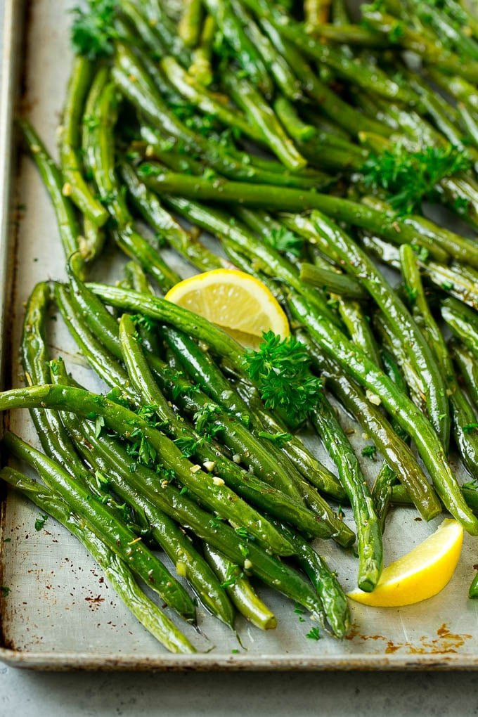 Roasted green beans on a sheet pan garnished with lemon and parsley.