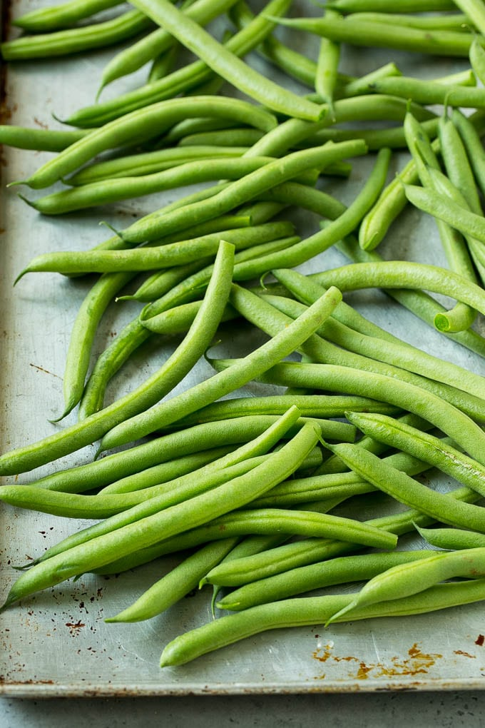Raw green beans on a sheet pan.
