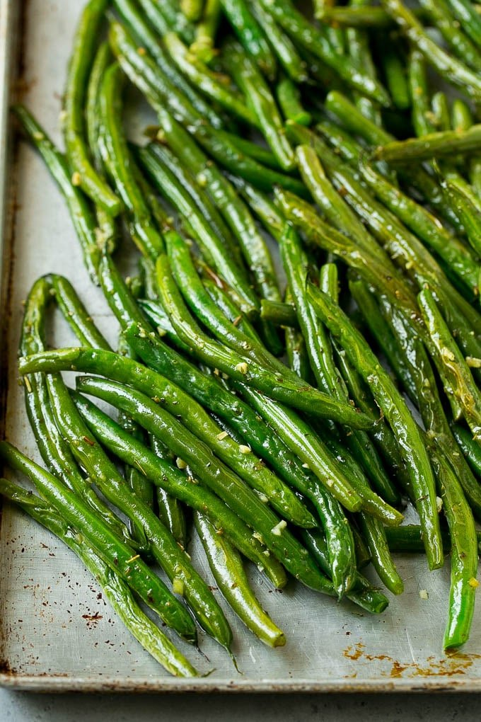Roasted green beans with garlic and herbs, on a baking pan.