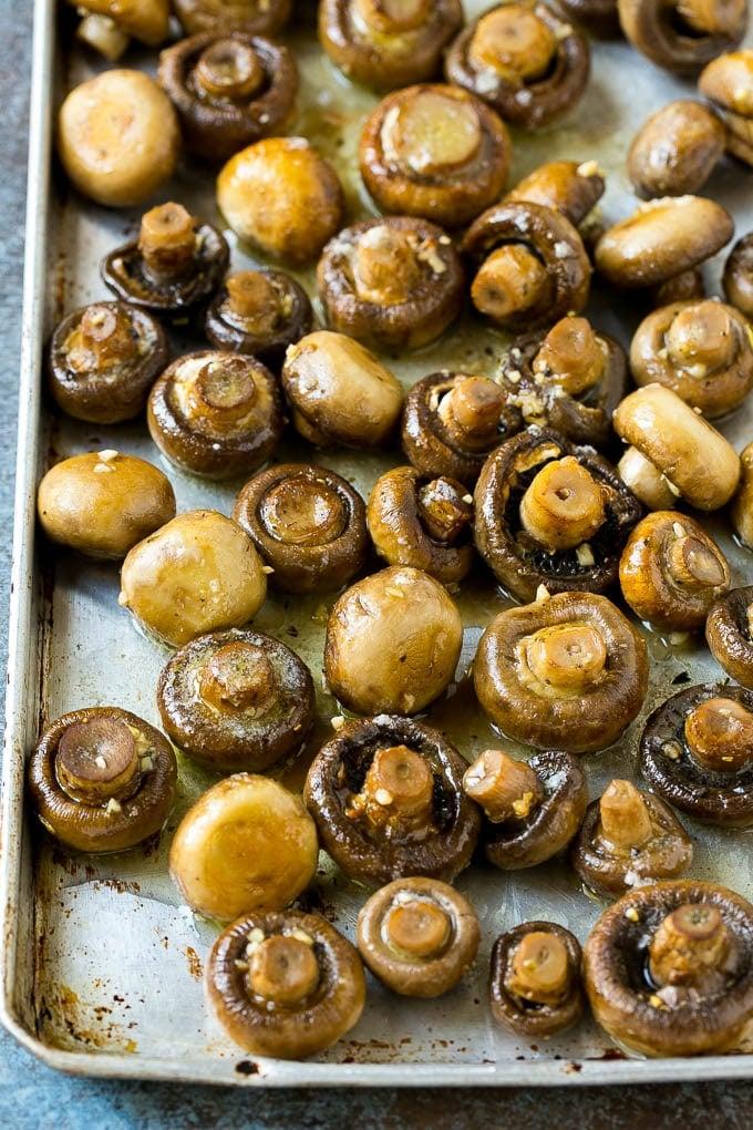 Roasted mushrooms in garlic butter on a sheet pan.