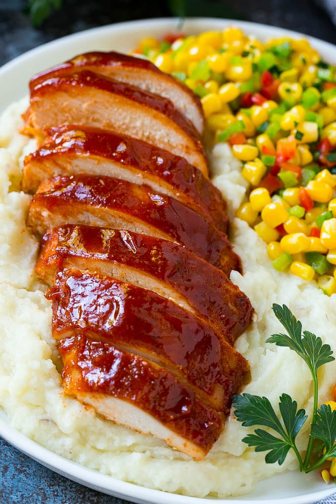 Sliced smoked chicken breast over mashed potatoes and corn.