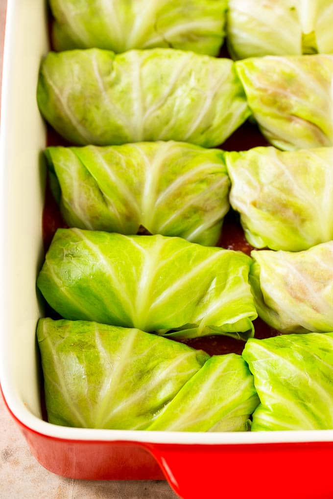 Cabbage leaves wrapped around beef and rice in a baking dish.
