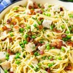 A skillet of turkey pasta carbonara with peas and bacon in a creamy sauce.