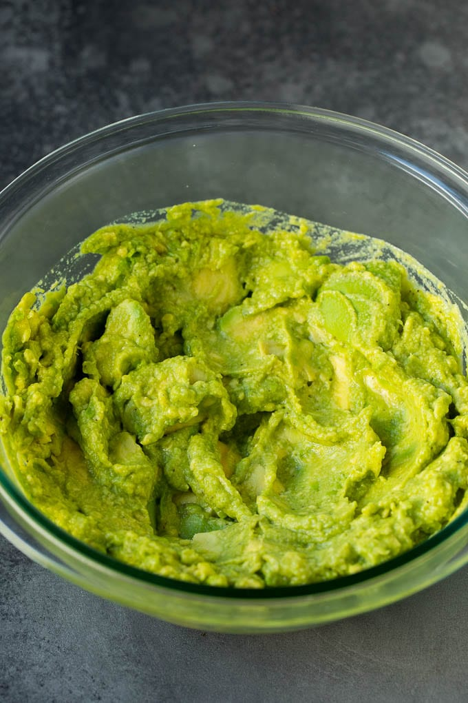 Mashed avocado in a mixing bowl.