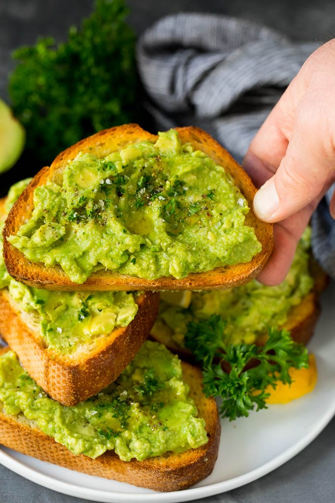 A hand holding a piece of homemade avocado toast.