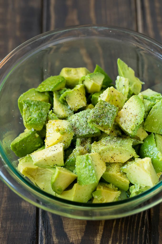 Diced avocado with lemon juice, olive oil, salt and pepper in a bowl.
