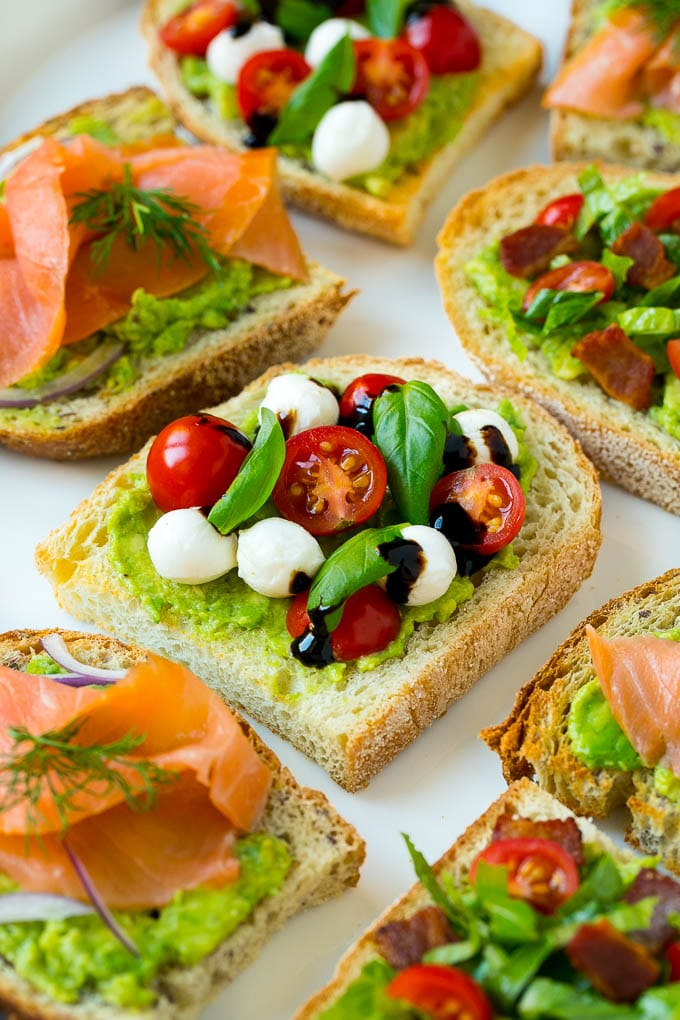 Three different flavors of avocado toast on a serving platter, including caprese, smoked salmon and BLT.