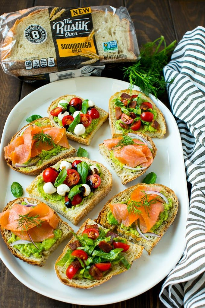 A platter of three flavors of avocado toast with fresh herbs for garnish.