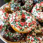 A serving plate of baked donuts frosted in dark and white chocolate and topped with sprinkles.