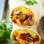 A cross section of a breakfast burrito filled with eggs, sausage, beans and cheese.