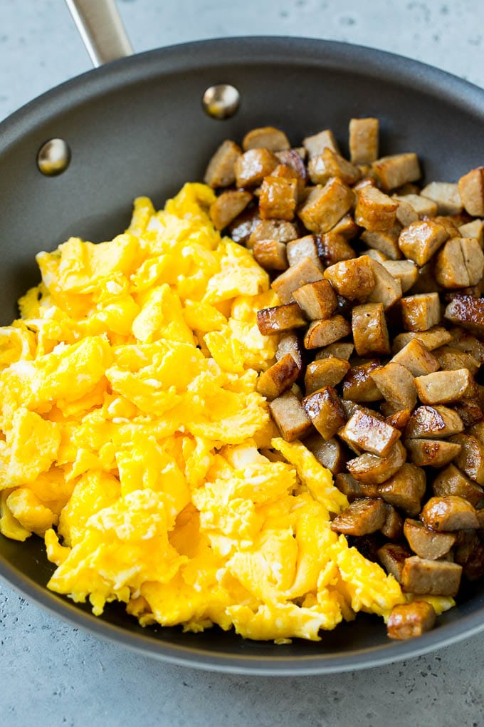 Diced sausage and scrambled eggs in a pan.