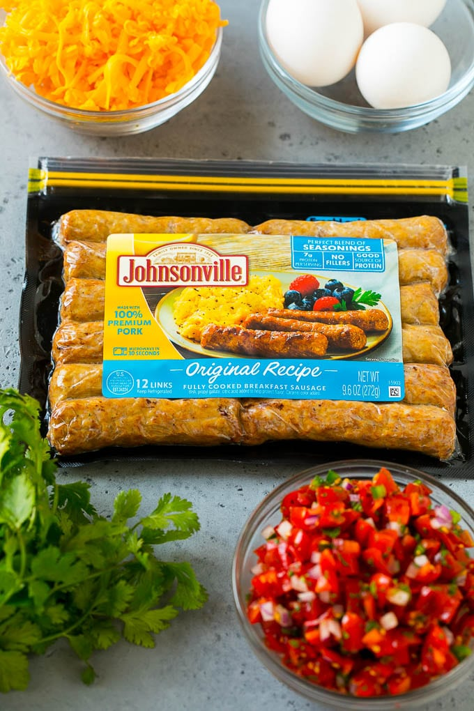 A package of sausage links along with bowls of pico de gallo, eggs and shredded cheese.