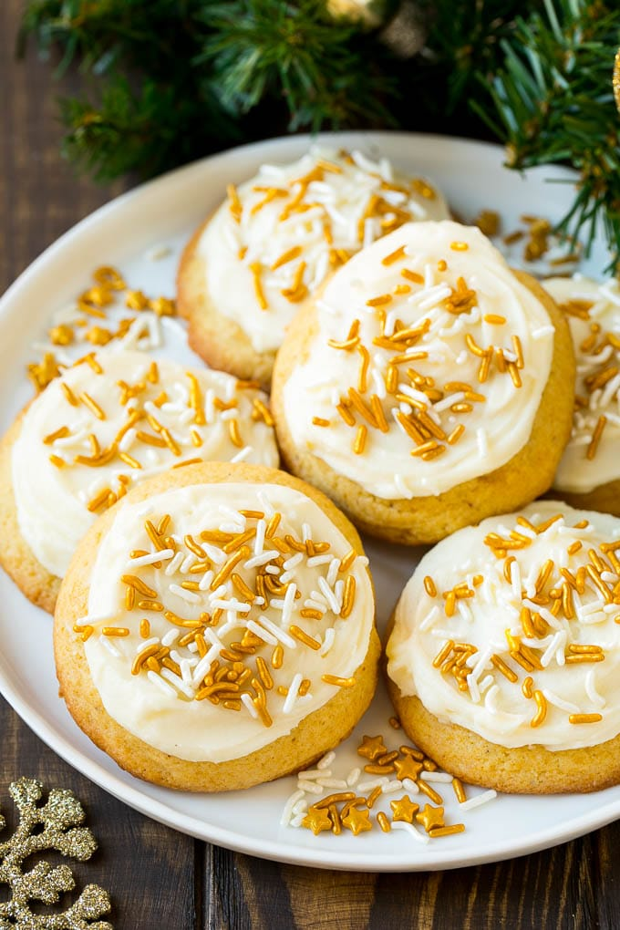 Eggnog cookies topped with frosting and gold sprinkles on a serving plate.