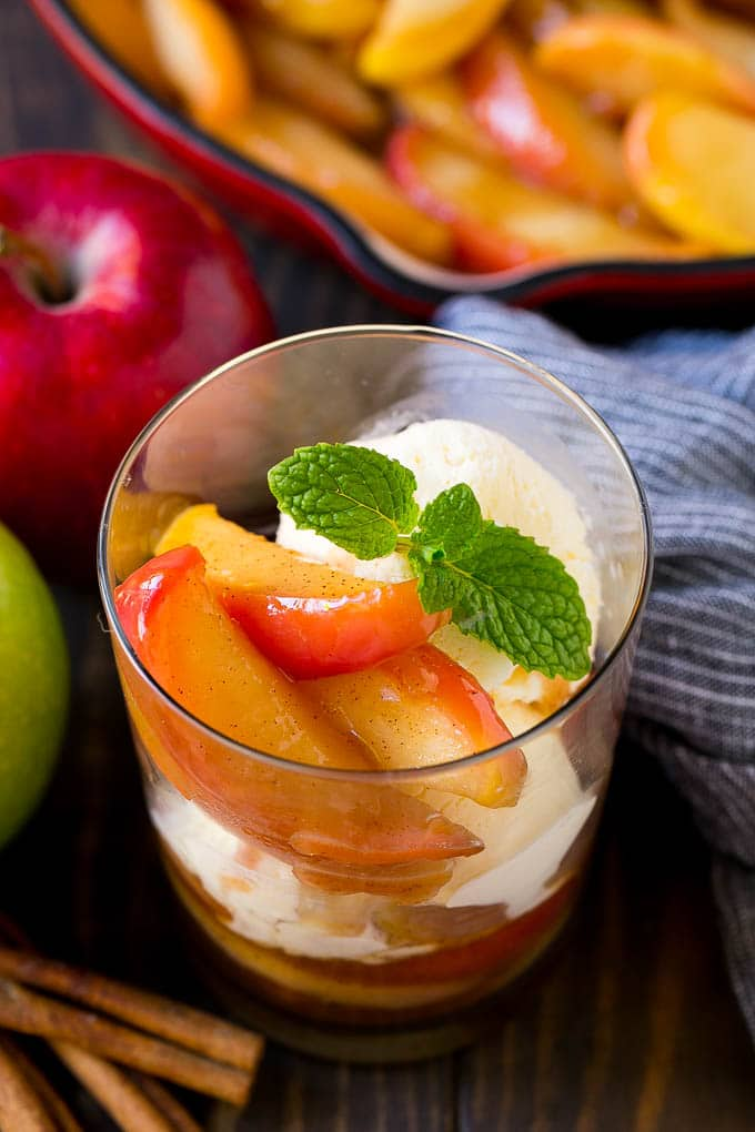 A cup of fried apples served with vanilla ice cream and garnished with fresh mint.