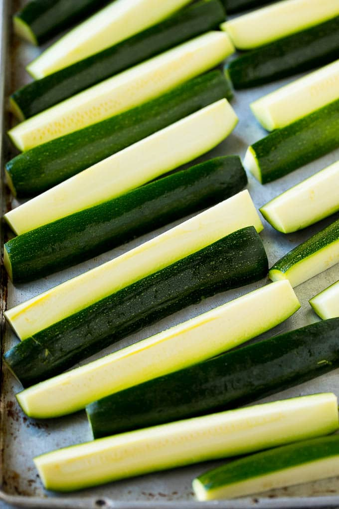 Sticks of zucchini on a sheet pan.
