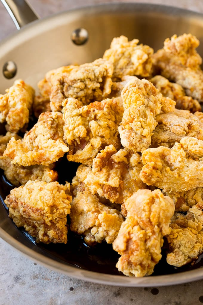 Fried chicken thigh pieces in a pan of sweet and savory Korean sauce.