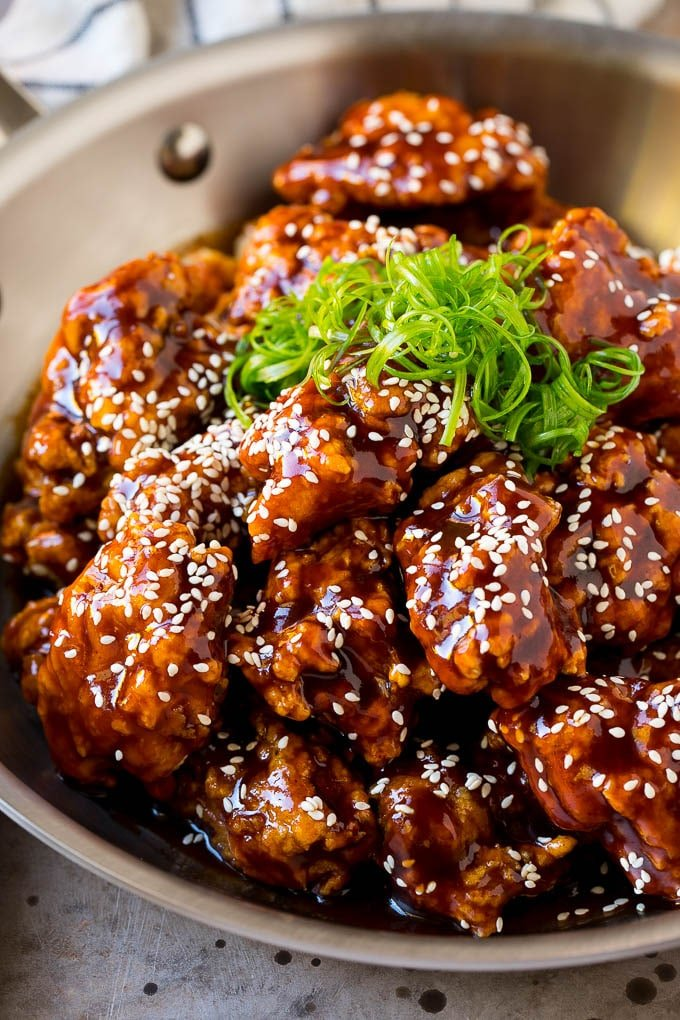A pan of Korean fried chicken coated in a sweet and spicy sauce then garnished with sesame seeds.