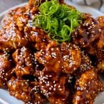 Korean fried chicken on a serving plate topped with curly green onions.