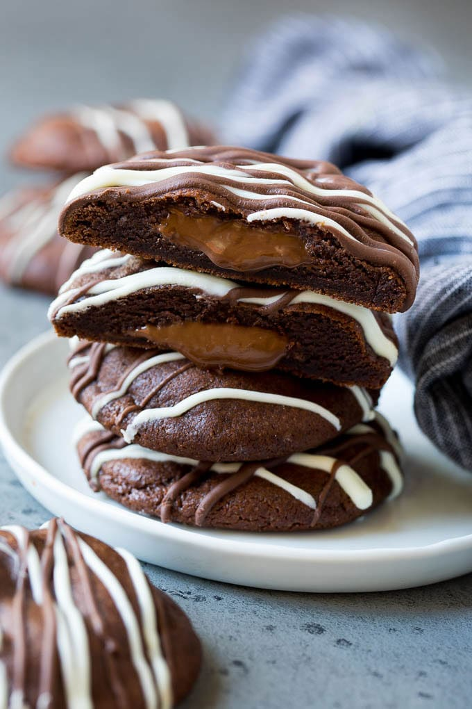 A stack of Nutella cookies on a plate with one cut open.